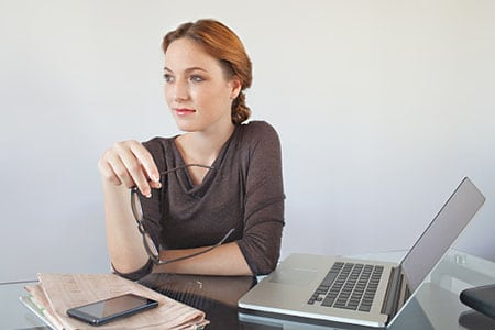 Professional woman sitting at workdesk with laptop