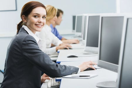 Portrait of busy woman sitting at the computer table and touching computer mouse on the background of businesspeople